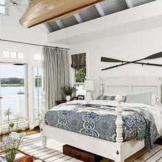 A flat woven rug in traditional blue-and-white looks just right beneath this master bedroom's coordinating bed and linens. Overhead, an antique canvas kayak reminds homeowners that the water is only steps away.