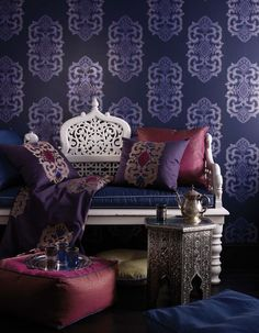 The Empress wallpaper, in dark violet and amethyst, is accompanied by pillows suited in Empress fabric in blackberry, cerise, and electric blue -- Matthew Williamson Designs Wallpapers and Fabrics for Osborne & Little