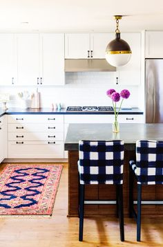 White and black kitchen with brass chandelier, purple accents, and patterned bar stools