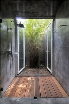 shower with an outdoor view  and wood floor.  This is what I want in my house, hands down.