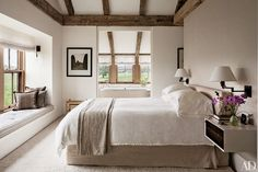 A Lynn Geesaman photograph is displayed in the master bedroom; the nightstand is by BDDW, and the rug is by Edward Fields. Manhattan-based Kathleen Walsh Interiors decorated the home, which is located on a Martha's Vineyard organic farm.