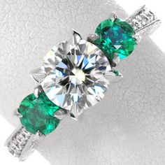 Glowing green emeralds makes this three stone ring a statement piece. A 1.00 carat center diamond is proudly accented over a lotus style petal design with diamond embellishments.