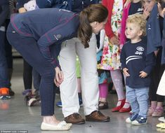 Adorable: Kate bent down to speak to one curly-haired youngster who looked happy to see he...