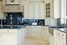 White cupboards over beige marble flooring surround a dark blue marble backsplash and countertops in this kitchen.