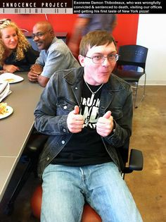 Exoneree Damon Thibodeaux, who was sentenced to death and wrongfully imprisoned for 15 years before he became the 300th person proven innocent by DNA testing, is seen here visiting the Innocence Project offices and getting his first taste of New York City pizza. Exoneree and Innocence Project board member Marvin Anderson is in the background.