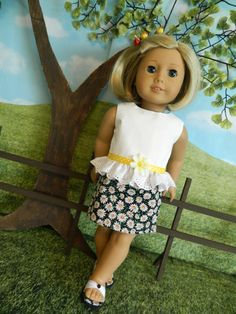 Cute little summer outfit made to fit your American Girl doll or similar 18 doll.  Top and skirt are made of 100% high-quality cotton fabric. Top is made of white fabric that has a little design in it. A ruffle of white eyelet is gathered around the bottom edge of top. Accented with a yellow ribbon sewn around gathering and a daisy flower. Top is fully lined and closes in back with velcro.  Skirt is made of daisy print cotton fabric, black background with white and yellow daisies printed on…