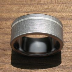 The unique texture of this brushed titanium ring, only achieved on a hand-driven lathe glimmers and reflects the light. The captivating ring features an offset inlay pinstripe of argentium silver, and arrives with a buffing pad so you can maintain the stunning finish.