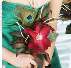 Cheryl's maids carried small arrangements made by the bride's friend of one magnolia and a peacock feather. The bridesmaid bouquets matched Cheryl's bouquet, which was also made up of feathers and magnolias.