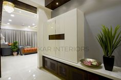 Off-white Coloured Wooden Storage Cabinet in a Foyer Area, Extra Storage below, Indoor 🍀 Plant & Recessed ✨ Lighting for the Ceiling - GharPedia Space Interiors, Storage Units, Center Table, Off White Color, Cabinet Design, Extra Storage, Indoor Plants, Foyer, Ceiling