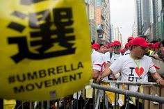 Umbrella Revolution Hong Kong, A banner featuring the words 'Umbrella Movement' stands as workers prepare to dismantle a barricade on Nathan Road in the Mong Kok district of Hong Kong, China, on Wednesday, Nov. 26, 2014. Street skirmishes broke out at a pro-democracy protest site in Hong Kong as police officers cleared make-shift barricades at a key road in Mong Kok. Photographer: Brent Lewin/Bloomberg via Getty Images