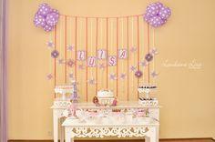 Mesa do bolo, mesa de guloseimas. Atrás, painel de fitas com nome da aniversariante, mandalas de papel e cataventos decorativos.
