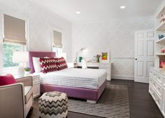 Bedroom: Bedroom Design With Pursuit In Mind. girl room decor. purple bed. chevron cushions. soft patterned wallpaper. chevron ottoman. chevron textured rug. clean line accent chair. folded roman shade. white study desk. white cabinet.