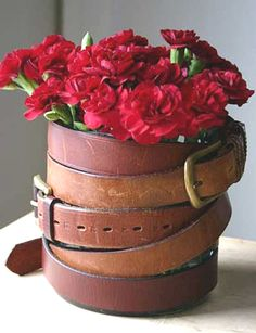 Old belts from the thrift store, flea market or yard sale.  Wrap them around old coffee cans...great look!