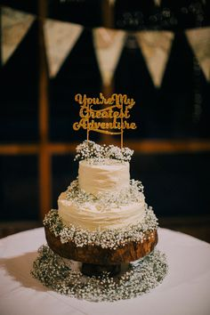 Tiered wedding cake with 'You're my greatest adventure' gold glitter wedding cake topper and baby's breath // KS and Avis' Mountain Garden Nuptials at Tanarimba Janda Baik {Facebook and Instagram: The Wedding Scoop}