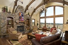 My husband loves lodge-style homes and this one would suit me fine with a window like that.  Not sure about the fireplace but the arched ceiling beams are magnificent.