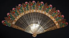 an early 19th century carved horn fan. The horn sticks are finely carved and painted with beautiful flowers