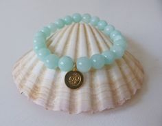 aqua jade yoga bracelet  gold om charm   crystal healing  by beachcomberhome, $20.00 jade is a symbol of serenity and purity. it signifies wisdom gathered in tranquility. it increases love and nurturing. a protective stone, jade keeps the wearer from harm and brings harmony. jade attracts good luck and friendship.