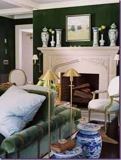 Hunter / dark green painted living room walls - Marble fireplace - Green sofa - Blue, white, and brass accents