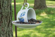 Use a tube of E6000 glue to glue the cup to the saucer, then let it sit overnight.  fill  it with sunflower seeds and general seed and hang it from a shepherd's hook near the birdbath.  From Country Musings.