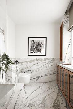 Add warm wood tones to a heavy veined marble bathroom