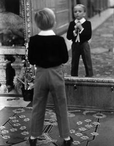 Alfred Eisenstaedt, English Boy Using Reflection in Mirror in Foyer of Grand Hotel to Fix His Tie