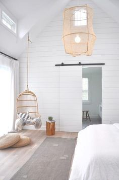 Under a vaulted ceiling, a white shiplap wall frames a shiplap bar door concealing an en suite bathroom, while a Two's Company Hanging Rattan Chair hangs in a corner between seagrass cushions and a wood stump stool placed on a gray wash wood floors in front of a window dressed in white curtains.