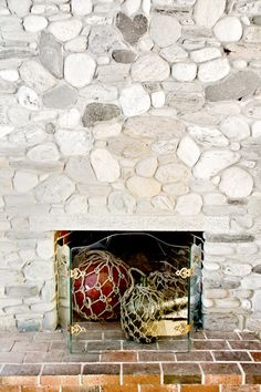 fireplace from beach rocks House On The Rock, Beach Rocks, Painted River Rocks, River Rock Fireplaces, Whitewash Stone Fireplace, Design Sponge, Fireplace, Glass Fireplace Screen, Diy Fireplace