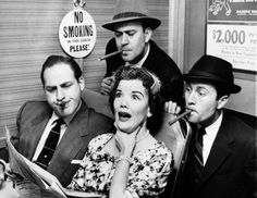 """Photo honoring Sid Caesar on Tributes.com. """"Nanette Fabray, seated at right, gagged as railroad commuters Sid Caesar, left, Carl Reiner, top, center, and Howard Morris poked their smokes in her direction while looking over her shoulder to read her newspaper, on """"Caesar's Hour,"""" April 27, 1955. """""""