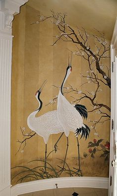 Asian cranes painted on striped wallpaper.