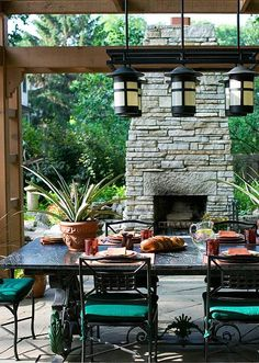This is a wonderful outdoor dining area. I love the stacked stone fireplace and pendant lighting.