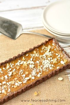 Easy gluten free pumpkin tart with white chocolate, candied ginger, and dark rum. This tart is perfect for entertaining. Recipe at http://www.fearlessdining.com