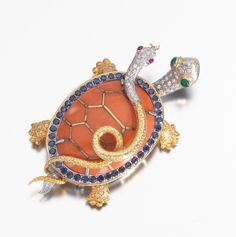 18K Gold, Diamond & Coral En Tremblant Turtle & Snake Brooch Coral turtle with 18K white and yellow gold, depicting a turtle with snake on it's back, the shell os coral and surround set with 43 sapphires apprx 2 carats, the heads with sixty pave set diamonds apprx .50 carats. The snake eyes are .04 carat cabochon rubies and the turtle has two .12 carat emerald eyes.