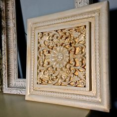 """This plaque was painted a creamy white and aged with a golden finishing wax to bring out its delicate and intricate details. It measures 12"""" x 12"""". It can hang on the wall or be propped with other frames or mirrors. Because of its age it has a slight """"ding"""" on one corner. I have included a photograph of this area. I believe this does not take away from its beauty but enhances it. As with all my pieces I have hand painted them so there"""