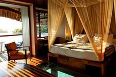 Bedroom in a lone thatched island house with glass floors.. Bora Bora islands..