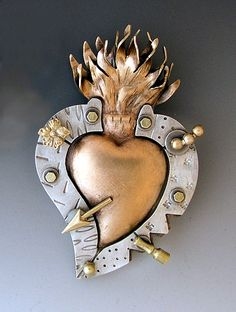 """Milagro Heart""  Metal Pin    Created by Thomas Mann  Inspired by Mexican talismans for love, healing, and protection, this silver, bronze, and brass brooch may be just the cure you need. Collage items will vary slightly."