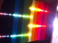Gekleurde wol gespannen tussen gordijnrails met led licht erachter. Regenboog kleuren - diy rainbow - string art diy