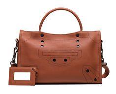 Balenciaga's Blackout City bag includes a detachable shoulder strap and leather-bound travel mirror. (=)