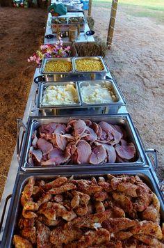Country buffet for a wedding reception under an open barn.  Chicken tenderloin in herb sauce, dinner ham, mashed potatoes, green beans, buttered corn, slaw, rolls.