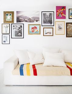 Dress up a while couch with a colorful striped throw and a punchy gallery wall via @dominomag