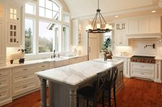 Halcyon House LTD    Fantastic two-tone kitchen design with white kitchen cabinets, marble counter tops, gray kitchen island, Pottery Barn Aaron Black Counter Stools, oil-rubbed bronze pot filler, warming drawers, farmhouse sink and Pottery Barn Veranda Round Chandelier.