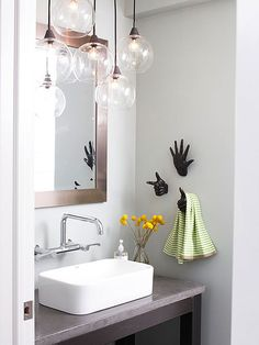 Make the most of a small nook in your bathroom by outfitting it with a made-to-fit vanity. A wall-mount faucet works particularly well in a narrow area, where there might otherwise not be room for a sink and fixture. Installing interesting towel hooks on the wall adds personality and keeps washcloths close without taking up valuable counter space.