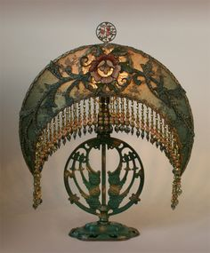 Wonderful circa 1915 cast lamp base with original paint. The large Craftsman crescent shade is created with original Arts & Craft textiles in gold and green tones including antique bronze-gold metallic lace, net lace and an ornate period William Morris style rose and vine appliqué. Hand beaded custom fringe in accent colors of olive, earth tones and rose adorns the bottom of the shade