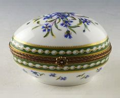 A Marie Antoinette pattern porcelain trinket box by Ancienne Royale in Limoges, France. This white porcelain oval box is painted with delicate purple flowers and edged in a green and gold tone border, with gold tone metal rim and floral clasp. The hinged lid opens to a small painted flower on the interior. Box is marked '1737 Ancienne Manufacture Royale de Limoges France,' a trademark of P.V. Porcelain in Limoges, France.