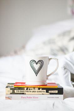 Livros feministas em cima da cama com uma caneca com coração em cima. Para poder viver (Park), Do que é feita uma garota (Caitlin Moran) e Sejamos todos feministas.  Post com fotos de livros e vídeo com o book haul do mês de maio falando sobre os livros novos que ganhei e comprei durante o mês.