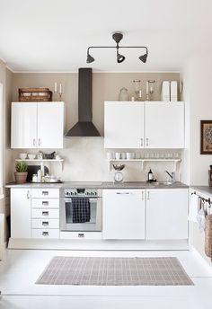 Keittiön valkoiset kaapit ja kauniit astiat korostuvat savensävyistä seinää vasten. Välitilaan Niina ja Ossi valitsivat Decosin betonipintaa muistuttavan sisustuslaastin. Musta liesikupu on Ikeasta ja metallinen talousvaaka löytyi Tiirinkosken tehtaalta Hämeenlinnasta.