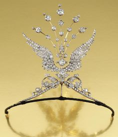 DIAMOND WING AIGRETTE TIARA, 1900. Designed as a pair of opposing scrolls surmounted by two out swept wings terminating in an aigrette of radiating knife-edge bars set throughout with circular-cut diamonds, original fitted case, accompanied by two brooch pin fittings, three tiara frame attachments, a diamond-set suspension bail and a hair pin/aigrette fitting, tiara/aigrette all detachable and may be worn in five combinations, wings detachable for wear as individual brooches.