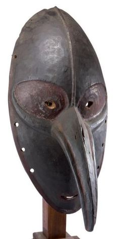 "Stylistic area of ​​the lower Sepik. (New Guinea) Important mask eyed joining at the root of a large nose down in the mouth slit along the classic shape of a bird's beak. Important remnants of red and black pigments, the back door an old label ""The Corneur - Roudillon."" Bois.h.: 53 cm"