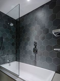 Bathroom Tile Ideas - Grey Hexagon Tiles // Hexagon tiles in various shades of grey line the walls in the 2-in-1 bath and shower in this bathroom.