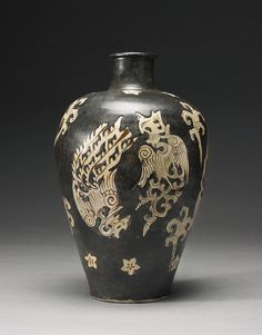 A LARGE AND UNUSUAL 'JIZHOU' 'PHOENIX' MEIPING SOUTHERN SONG DYNASTY the sides of the gradually flaring body rising to a rounded shoulder and narrow waisted neck with lipped rim, resist-decorated around the exterior with two pairs of phoenix in flight, divided by swirling cloud scrolls and a band of prunus blossoms around the base of the neck and above the foot, all reserved on a rich dark brown slip, the footring unglazed to reveal the pale buff body Height 14 1/4  in., 36.2 cm 100/200000…