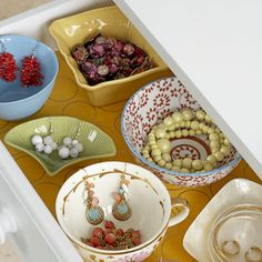 Mix and Match    Function gets fancy when you fit a drawer with pretty mismatched china that you have around the house (or get for pennies at a yard sale). Stack bangles in a saucer; dangle earrings over bowls, or fill them with necklaces or beaded bracelets. Line the drawer with decorative paper for contrast.     Tip: Use sticky-backed Velcro strips on the bottoms of your cups and bowls to keep them from sliding around